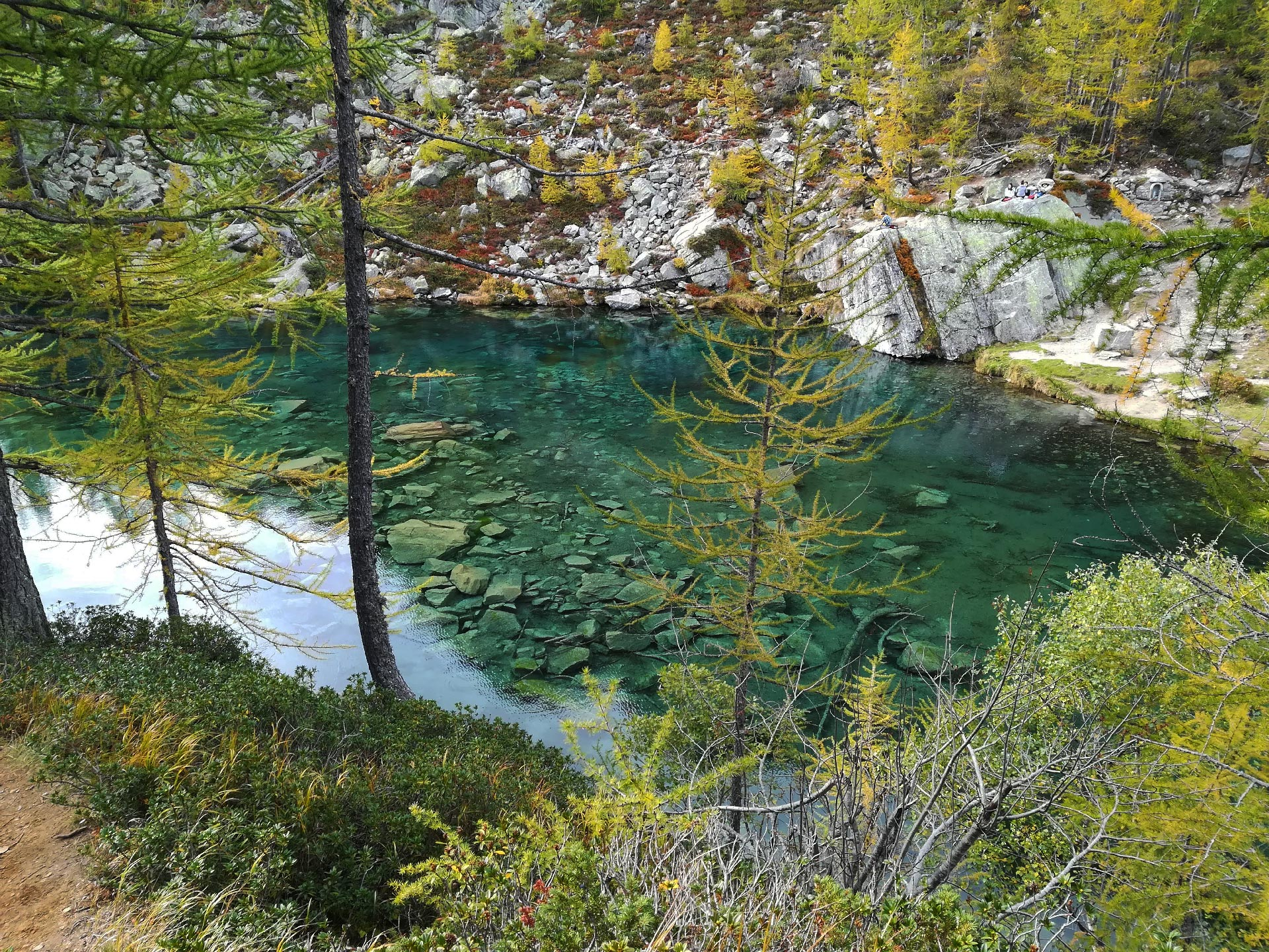 scorcio del lago delle Streghe dalle acque cristalline, abeti dai colori autunnali